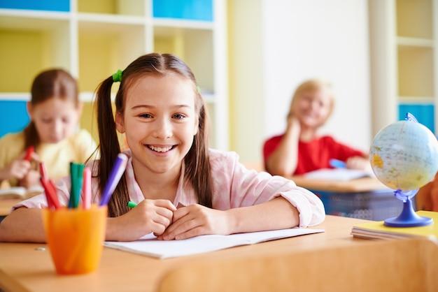 Fille avec un grand sourire dans une salle de classe