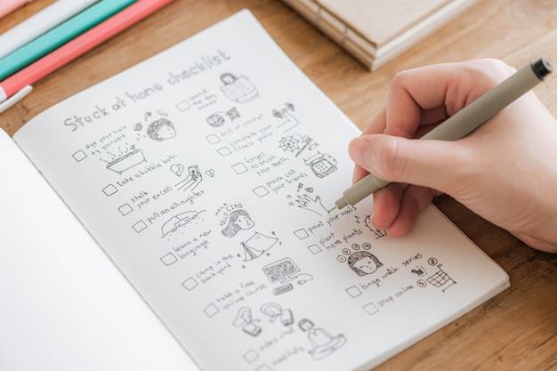 Fille griffonnant et faisant une liste de contrôle dans un cahier