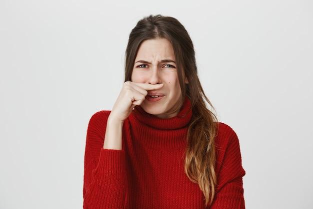 Fille grimaçant, nez fermé d'odeur dégoûtante