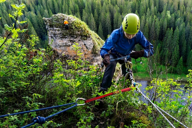 La fille de grimpeur vérifie l'équipement de sécurité tout en se préparant à descendre de la falaise au-dessus de la rivière