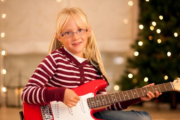 Fille avec guitare devant l'arbre de noël
