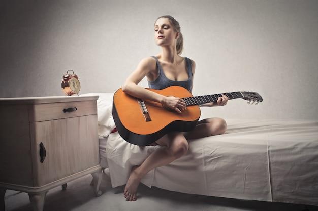 Fille avec une guitare sur un lit