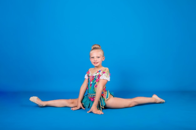 Une fille de gymnaste dans un beau costume se trouve dans une division longitudinale sur un mur isolé bleu
