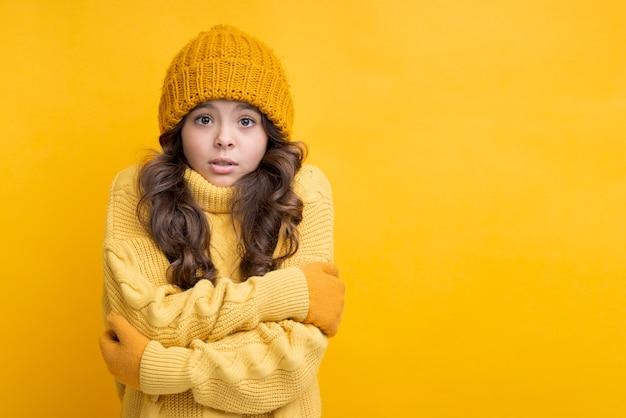 Fille habillée en jaune avec les mains croisées