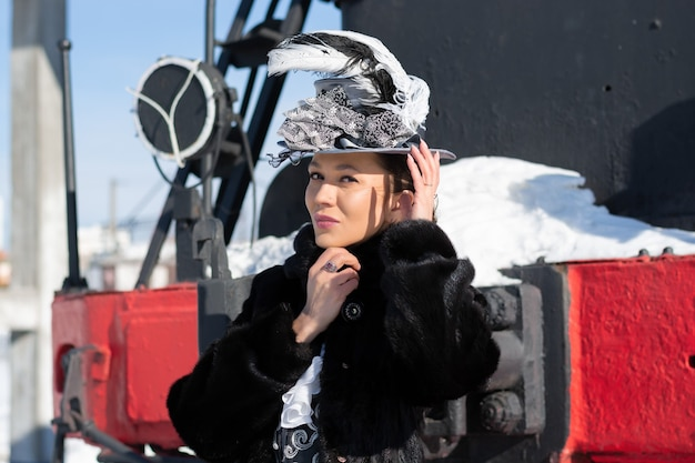 Fille habillée en noble du 19e siècle près d'une locomotive à vapeur. hiver russe