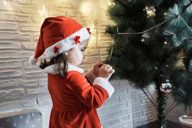 Une fille habillée en père noël décore un arbre de noël