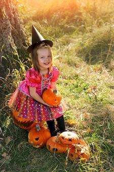 Une fille habillée en sorcière est assise avec une citrouille dans les mains à l'halloween