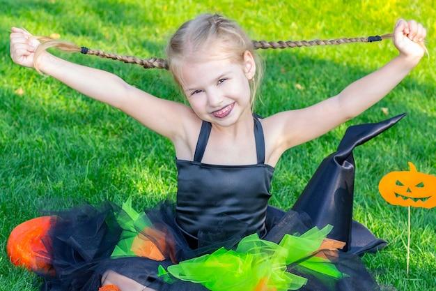 Fille habillée en sorcière pour la fête d'halloween. fille heureuse tenant ses tresses