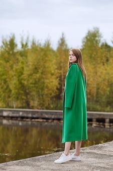 Fille en habit vert se promène au bord du lac