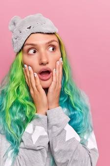 Une fille haletant d'émerveillement garde les mains sur les joues détourne le regard avec une expression choquée a de longs cheveux teints vêtus de vêtements de nuit et d'un masque de sommeil isolé sur rose