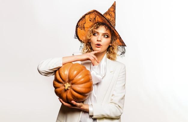 Fille d'halloween à la citrouille. femme en costume de sorcière. 31 octobre. la charité s'il-vous-plaît.