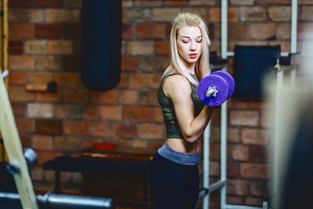 Fille avec haltère en gym