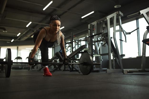 Une fille handicapée est engagée dans la salle de gym une femme avec une jambe s'entraîne avec un entraîneur, elle travaille dur et n'abandonne pas devant les ennuis