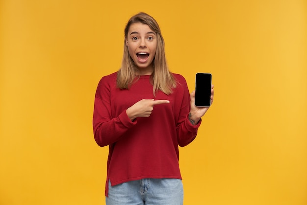 Une fille heureuse a l'air étonnée, la bouche largement ouverte d'excitation, garde le téléphone portable dans sa main, l'écran noir tourné vers l'appareil photo, pointe dessus avec l'index