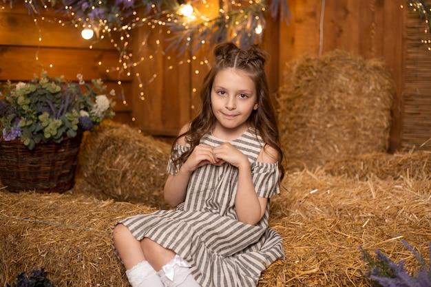 Fille heureuse assis dans des gerbes de paille en ferme portant une robe