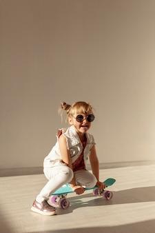 Fille heureuse, assis sur une planche à roulettes