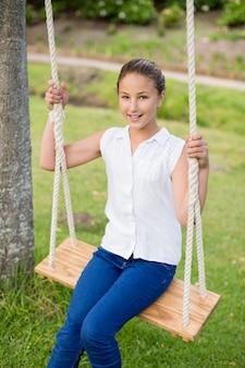 Fille heureuse assise sur une balançoire dans le parc