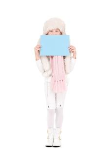 Fille heureuse au chapeau d & # 39; hiver avec tableau blanc