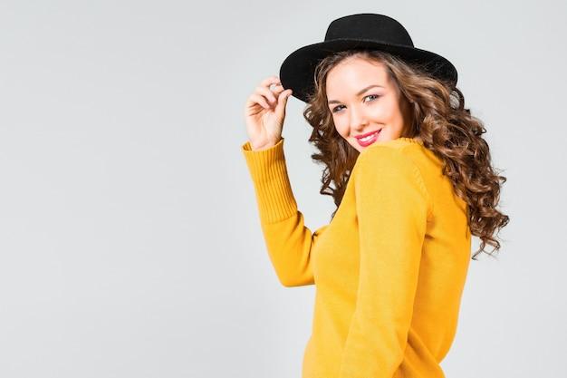 La fille heureuse au chapeau sur le mur gris du studio