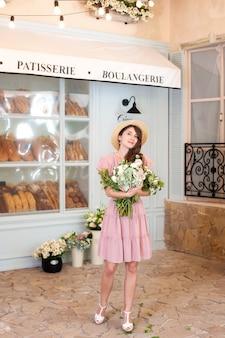 Fille heureuse au chapeau de paille tenant un bouquet de fleurs près du café de la rue