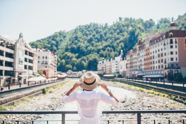 Fille heureuse au chapeau sur le quai d'une rivière de montagne dans une ville européenne.