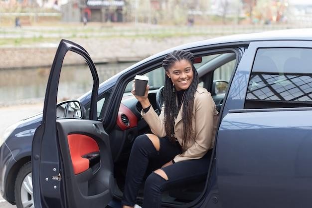 La fille heureuse au volant d'une voiture, boire du café, afro-américain