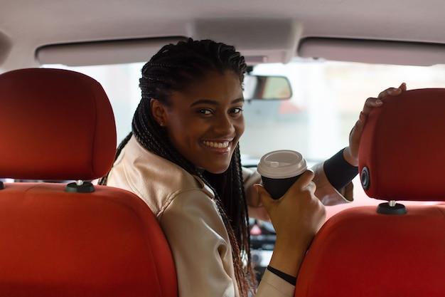 Fille heureuse au volant d'une voiture, boire du café, afro-américain