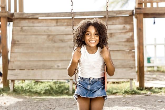 Fille heureuse aux cheveux afro ethnie latino-américaine assise sur une balançoire. concept d'amusement et de loisirs.