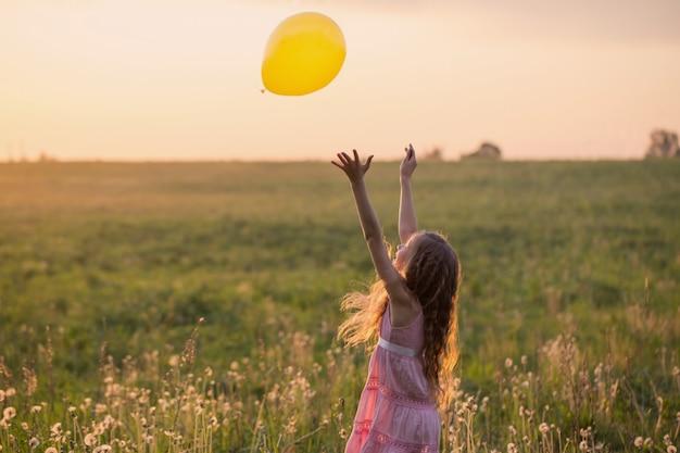 Fille heureuse avec ballon au coucher du soleil