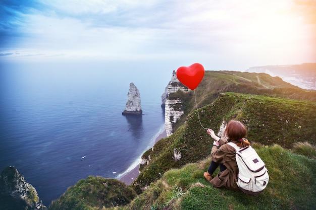 Fille heureuse avec un ballon rouge en forme de coeur à fond de décor etretat. la france