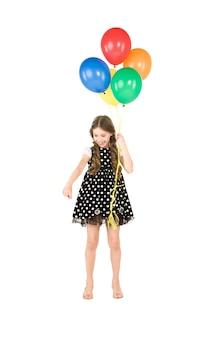 Fille heureuse avec des ballons colorés sur un mur blanc