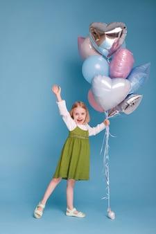 Fille heureuse avec des ballons sur une surface bleue en célébration