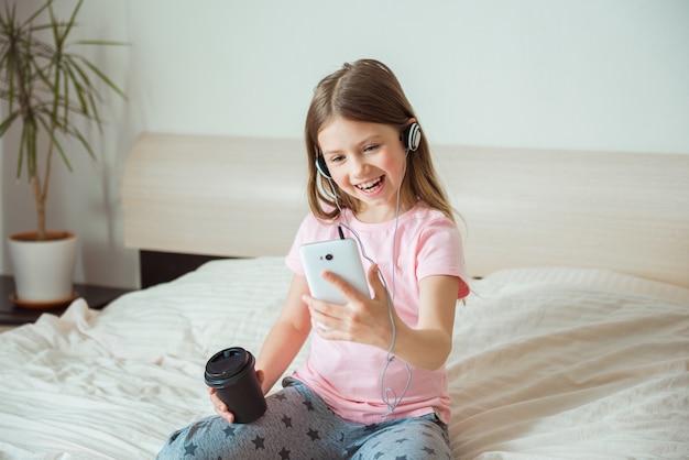 Fille heureuse bavardant en ligne à la maison sur le lit