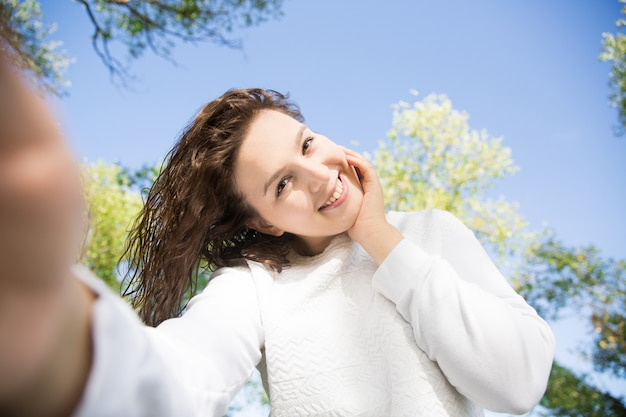Fille heureuse en blanc dans le parc vert. marcher sur la nature