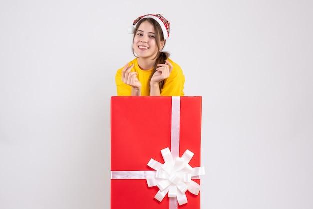 Fille heureuse avec bonnet de noel debout derrière un grand cadeau de noël sur blanc