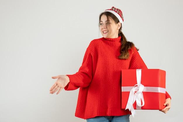 Fille heureuse avec bonnet de noel donnant la main tenant un cadeau sur blanc