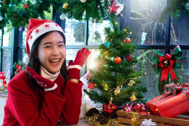 Fille heureuse en bonnet de noel et manteau rouge heureux avec sapin de noël et cadeaux, ambiance de noël