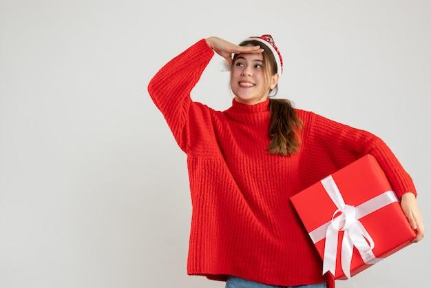 Fille Heureuse Avec Bonnet De Noel Mettant Sa Main Sur Son Front Tenant Un Cadeau Sur Blanc Photo gratuit