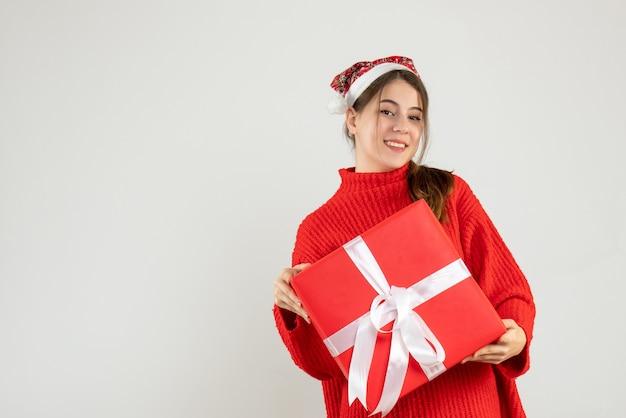 Fille heureuse avec bonnet de noel tenant son cadeau de noël sur blanc