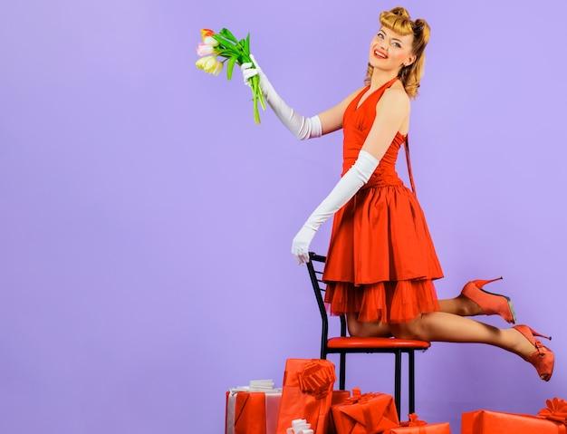 Fille heureuse avec cadeau et bouquet de tulipes, femme souriante en robe rouge avec fleurs et cadeau.