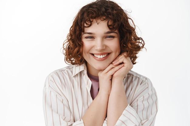 Fille heureuse candide, montrant de vraies émotions authentiques, riant et souriant, se tenant la main près du visage mignon, debout sur blanc