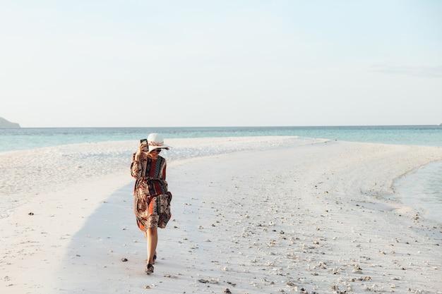 Fille heureuse en chapeau d'été et lunettes de soleil tenant un téléphone intelligent tout en courant et en jouant sur la plage