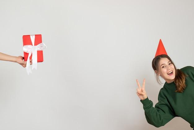 Fille heureuse avec chapeau de fête faisant un cadeau de signe de victoire dans la main de l'homme