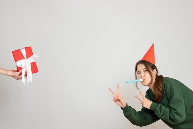 Fille heureuse avec chapeau de fête faisant signe de la victoire à l'aide de noisemaker main humaine tenant cadeau sur blanc