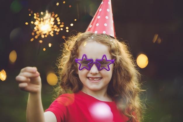 Fille heureuse en chapeau de fête avec sparkler brûlant.