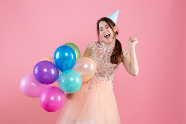 Fille heureuse avec chapeau de fête tenant des ballons sur rose