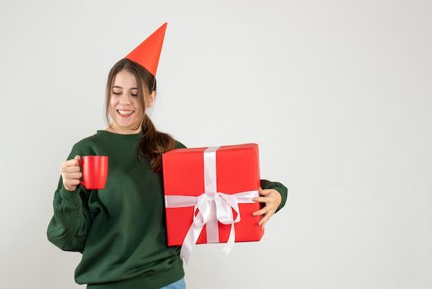 Fille heureuse avec chapeau de fête tenant son cadeau de noël en regardant une tasse sur blanc