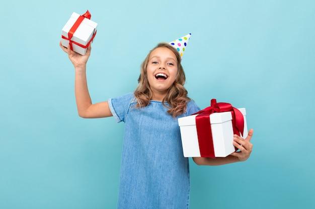 Fille heureuse avec un chapeau de vacances tient ses cadeaux