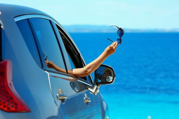 Fille heureuse de conducteur avec des lunettes de soleil dans la voiture en mer en été