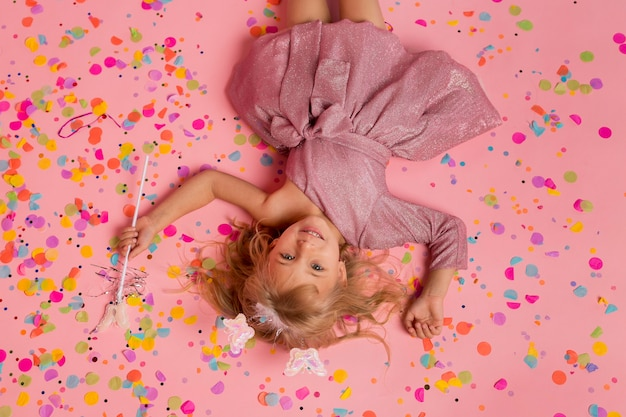 Fille heureuse en costume de fée avec des confettis et baguette